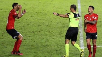Mauro Vigliano recibe las protestas de los jugadores de Independiente luego de sancionar el penal a favor de Racing. FOTO NA:MARCELO  CAPECE