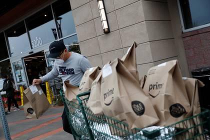 Excelso Sabulau, un conductor al servicio de Amazon Flex, usa una máscara protectora mientras lleva las entregas a su automóvil cerca de Whole Foods Market, en Dublín, California (REUTERS / Shannon Stapleton)