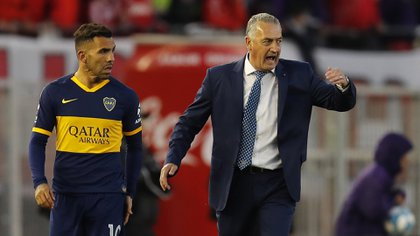 Boca Juniors' Carlos Tevez, left, is ready to substitute Alexis Mac Allister, next to coach Gustavo Alfaro, during an Argentine first division soccer game against River Plate in Buenos Aires, Argentina, Sunday, Sept. 1, 2019. (AP Photo/Natacha Pisarenko)