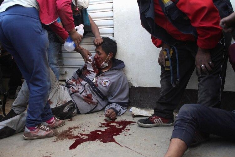 Un hombre herido es ayudado durante enfrentamientos cerca de la planta de gasolina en Senkata, en las afueras de El Alto, La Paz (REUTERS/Pablo Aneli)