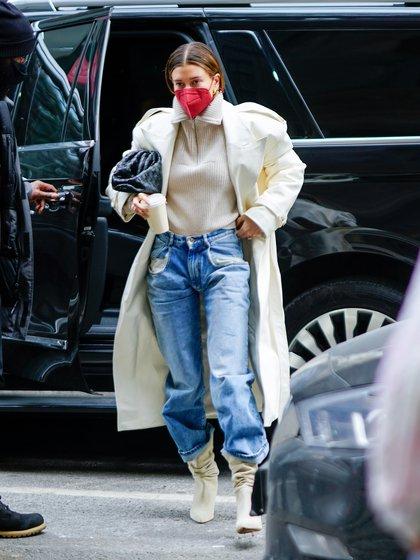 Durante sus vacaciones en Nueva York, Hailey Bieber asistió al estudio y lo hizo con un look trendy: jeans, botas, sweater y tapado. Todo en la gama del color clarito. Además, utilizó un tapabocas colorado y cartera negra