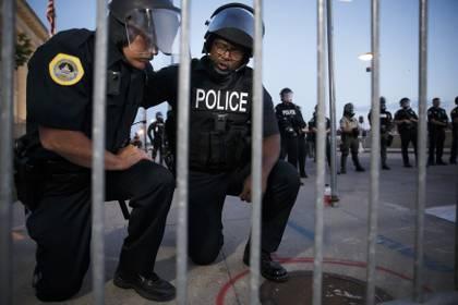 Los oficiales Irvin Franklin y Jack Kamerick se arrodillan y rezan en Des Moines (AP)