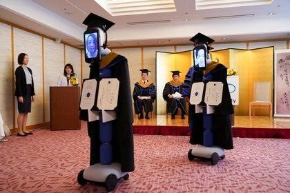Cuando se mencionaba el nombre del graduado, el robot que lo representaba se acercaba al presidente de la universidad, Omae Kenichi, que estaba en el escenario, para recibir el diploma. (BBT UNIVERSITY/Handout via REUTERS)