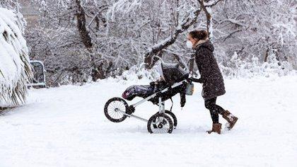 Una mujer intenta pasear a su bebé en medio de la nieve en Zaragoza (EFE/JAVIER BELVER)