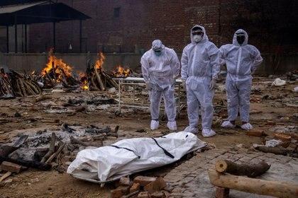 Hombres con trajes de protección permanecen junto al cuerpo de su familiar, fallecido por la enfermedad del coronavirus (COVID-19), antes de su cremación en un terreno del crematorio en Nueva Delhi, India, el 4 de mayo de 2021. REUTERS/Danish Siddiqui