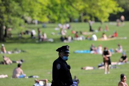 Un oficial del Departamento de Policía de la Ciudad de Nueva York (NYPD) con mascarilla observa cómo las personas se reúnen en el Sheep Meadow en Central Park durante el brote de COVID-19 en Manhattan, Nueva York. 15 de mayo de 2020. REUTERS/Andrew Kelly/File Photo