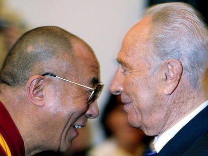 El ex presidente israelí Shimon Peres (d) junto al líder tibetano Dalai Lama (i), en la cuarta Cumbre Mundial de Premios Nobel por la Paz, en Roma. (EFE/Fotografía de archivo del 28 de noviembre de 2003)