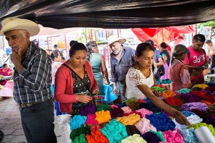 Unas mujeres compran el hilo de colores brillantes utilizado en el tipo de bordado hecho en los pueblos alrededor de Tenango de Doria, en el estado mexicano de Hidalgo.Credit...Celia Talbot Tobin para The New York Times