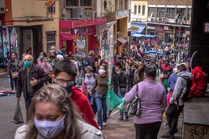 Peatones con tapabocas pasean frente a tiendas y vendedores ambulantes en la calle Ladeira Porto Geral en Sao Paulo, Brasil, el 30 de julio de 2020.