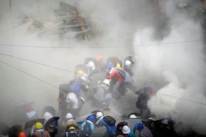 Gases lacrimógeno y extintores alrededor de los manifestantes mientras se refugian detrás de los escudos en un enfrentamiento con agentes de la policía antidisturbios durante una protesta contra el golpe militar en Yangon, Myanmar, el 1 de marzo de 2021. REUTERS