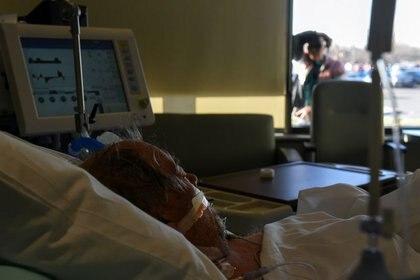 Daniel Benewiat, paciente de COVID-19, recibe tratamiento con un ventilador mientras su esposa, Tammy, lo observa desde una ventana en un hospital de la ciudad de Hutchinson, en Kansas. Noviembre 20, 2020. REUTERS/Callaghan O'Hare