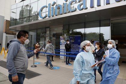 Personal de seguridad evita que se tomen fotografías en los exteriores de una clínica privada, este jueves en Lima (Perú), luego del acuerdo de último minuto alcanzado entre el Gobierno y las clínicas privadas.EFE/Paolo Aguilar