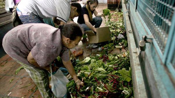 Un grupo de personas busca comida entre la basura de un mercado de Caracas. (Gentileza El Nacional)