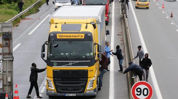 Inmigrantes intentan subir a un camión por la fuerza en Calais, rumbo a Reino Unido