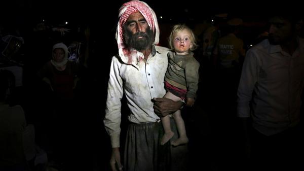 Un hombre yazidí con una menor, obligados a cruzar la frontera con Irak (AP)