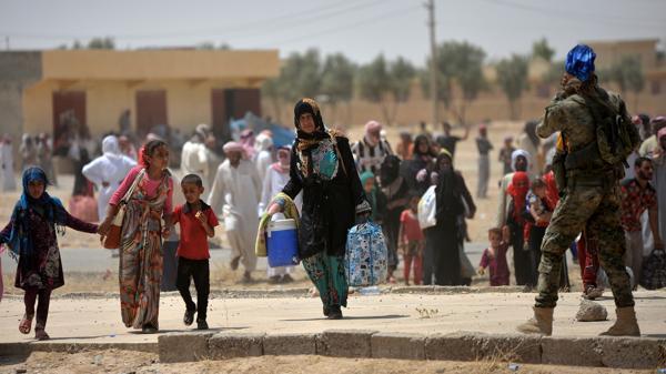 Una mujer camina junto a sus hijos bajo la custodia de un soldado del ejército iraquí. (Reuters)