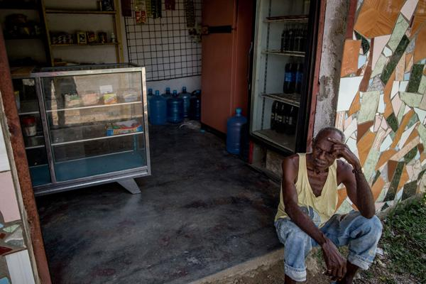 Un hombre descansa en la entrada de su tienda en Barlovento. Desde enero que no le reparten comida. Apenas subsiste (Washington Post)