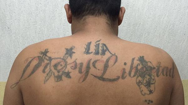 La espalda tatuada del sicario.