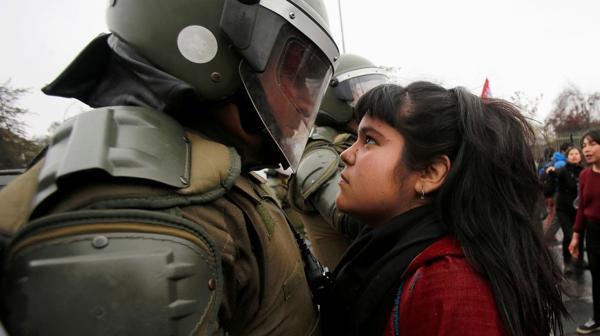 Una manifestante se enfrenta a un carabinero