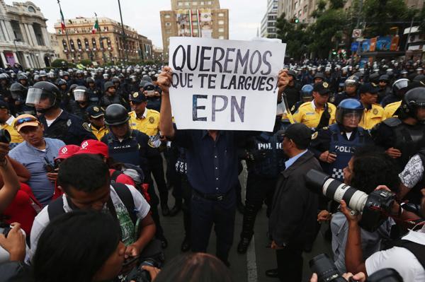 Un manifestante en Ciudad de México con un cartel que pide la renuncia del Presidente (Reuters)