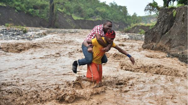 Un hombre rescata a otro para que no se lo lleve la corriente (AP)