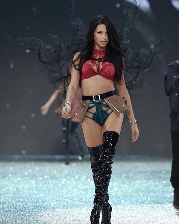 La legendaria Adriana Lima con un conjunto de encaje bicolor, alas negras, una falda de cuero y bucaneras charol. Una de las pasadas más hot durante el Victoria's Secret fashion show