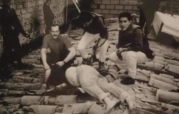 Pablo Escobar está tendido muerto en un tejado. Un agente de la DEA y policías colombianos posan junto al cuerpo del zar de la cocaína
