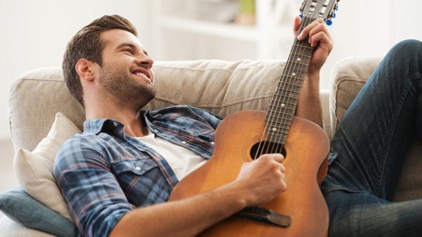 Un hombre tocando la guitarra y miles de mujeres suspirando por él (iStock)