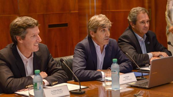 El ministro de Finanzas, Luis Caputo, acompañado a su derecha por el secretario del área, Santiago Bausili, y a su izquierda por el jefe de Gabinete de la cartera, Pablo Quirno